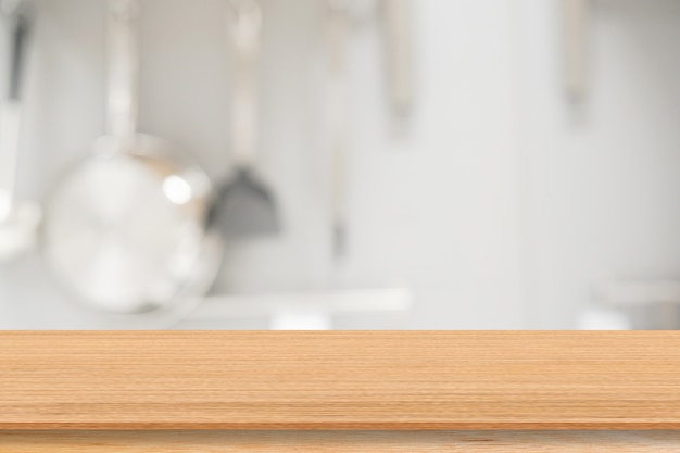 Desfocar dentro da cozinha moderna com equipamentos de cozinha e mesa de madeira para o show, promover o plano de fundo do produto