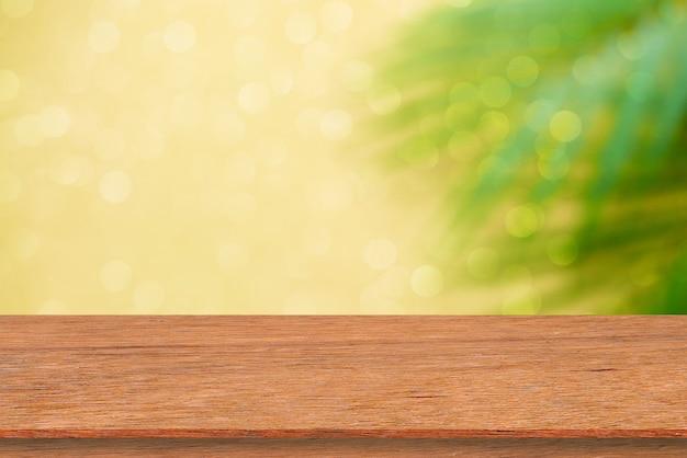 Desfocar folhas de coco tropicais em fundo amarelo com prancha de madeira marrom envelhecida