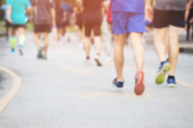 Desfocar foto grupo de pessoas multidão. pés de corredor de atleta fazendo exercício em pista de corrida na estrada