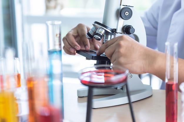 Desfocar imagens suaves do cientista usando um microscópio para inspeção do produto