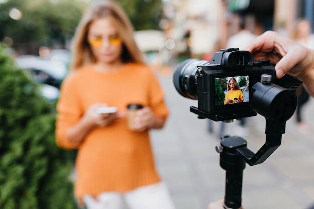 Desfocar o retrato de uma mulher de óculos amarelos com uma câmera preta em foco
