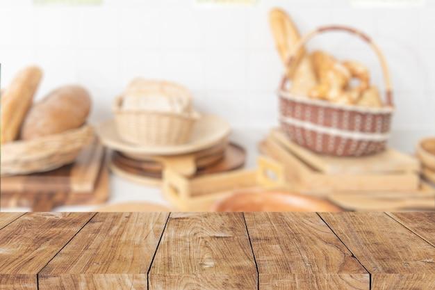Desfoque a cozinha da padaria de alimentos com o primeiro plano da mesa de madeira para o design do modelo de publicidade.