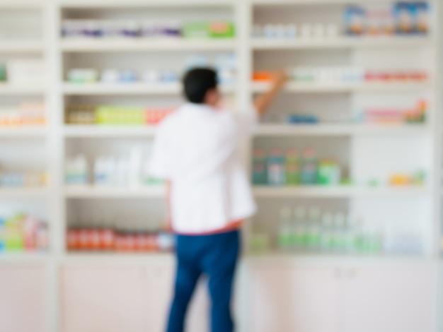 Desfoque a imagem do farmacêutico tomando remédio da prateleira da farmácia