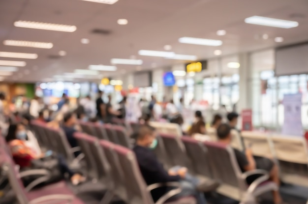 Desfoque abstrato e interior desfocado do terminal do aeroporto com viajantes
