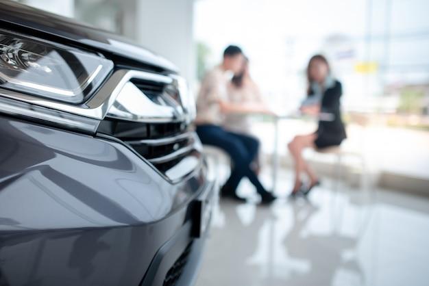 Desfoque de fundo os casais ficam felizes em comprar um carro novo no showroom e entrar em uma loja de carros. o conceito de compra de carro e o conceito de sucesso