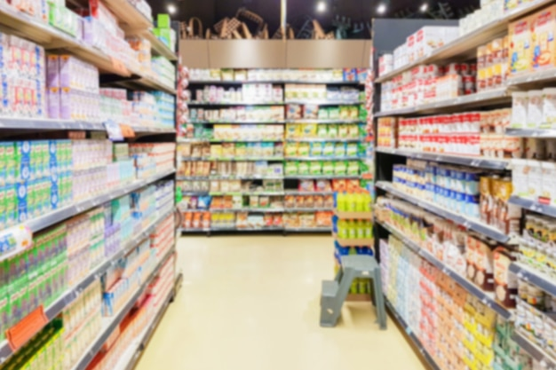 Desfoque de lente de corredor de supermercado com caixa de leite em prateleiras