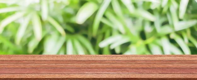 Desfoque o fundo da natureza com a luz do sol brilhante e o tampo da mesa de madeira simples moderna