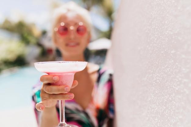 Desfoque o retrato do incrível modelo feminino com um copo de bebida em foco.