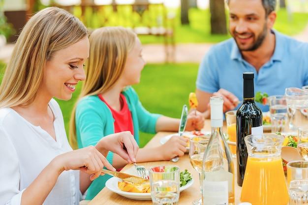 Desfrutando a refeição juntos. família feliz desfrutando de uma refeição juntos, sentados à mesa de jantar ao ar livre