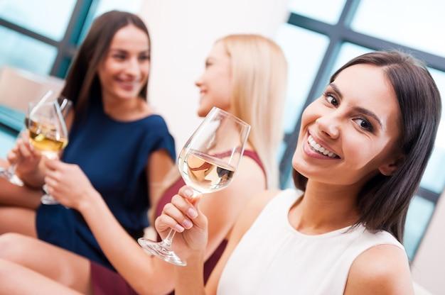 Desfrutando de bons momentos com os amigos. mulher jovem e bonita em um vestido segurando uma taça com vinho branco