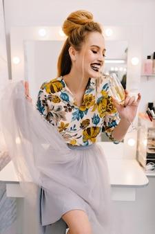 Desfrutando de momentos felizes em salão de cabeleireiro de modelo fashion com uma taça de champanhe