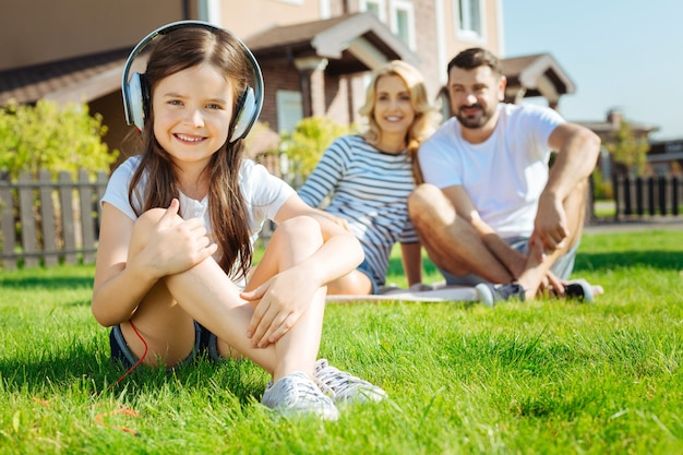 Desfrutando de música. adorável menina sentada na grama ouvindo música enquanto seus pais felizes sentados ao fundo e olhando para ela com admiração