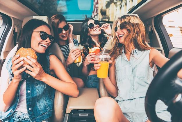 Desfrutando de seu almoço no carro. quatro lindas mulheres jovens e alegres olhando uma para a outra