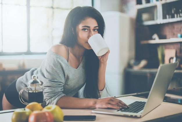 Desfrutando de um café fresco da manhã. mulher jovem e bonita de raça mista tomando café e olhando para a câmera enquanto se inclina na mesa da cozinha em casa
