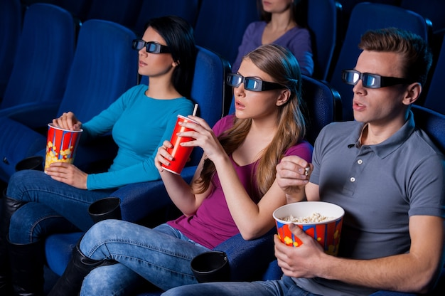Desfrutando de um filme tridimensional. vista superior de pessoas em óculos tridimensionais assistindo a um filme enquanto estão sentadas no cinema