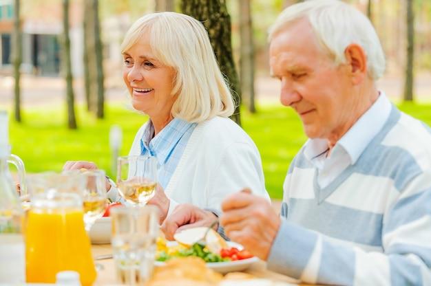 Desfrutando de um jantar ao ar livre. casal idoso desfrutando de uma refeição enquanto está sentado à mesa de jantar ao ar livre