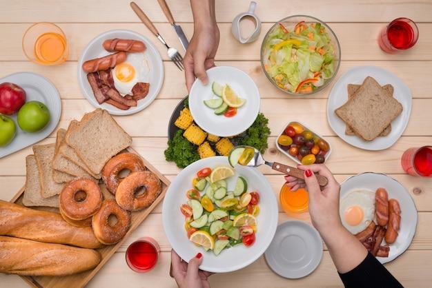 Desfrutando de um jantar com amigos. vista superior de um grupo de pessoas jantando juntos, sentados à mesa de madeira