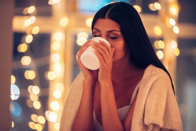 Desfrutando de uma bebida quente. mulher jovem e bonita coberta com um cobertor, bebendo café e mantendo os olhos fechados com luzes de natal ao fundo