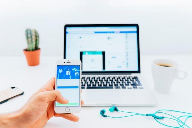 Desfrutando o facebook no telefone e no laptop