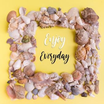 Desfrute das letras do dia-a-dia em um pedaço de papel sobre conchas e estrelas do mar. texto de motivação de verão plana lay