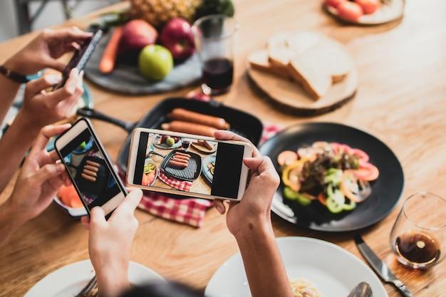 Desfrute de jantar comendo festa e comemoração com amigos e tirando foto por telefone