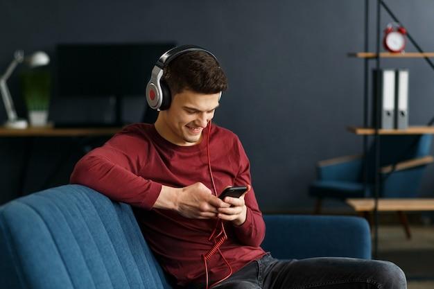 Desfrute de ouvir música. jovem em fones de ouvido, ouvindo música no telefone inteligente usando o aplicativo de música. retrato de cara em fones de ouvido e celular em casa. relaxamento, lazer e gerenciamento de estresse.