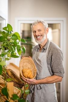 Desfrute de sua refeição. homem grisalho barbudo e alegre com avental mostrando croissant fresco na cesta de pé na padaria