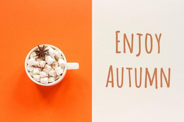 Desfrute de texto de outono e chocolate quente com marshmallows em fundo bege laranja. humor de outono conceito.