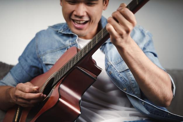 Desfrute de um belo homem asiático praticando ou tocando violão no sofá da sala de estar