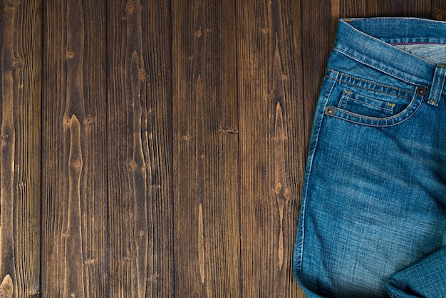 Desgastado, jeans ou azul jeans denim coleção no fundo da mesa de madeira escura áspera, vista superior com espaço de cópia