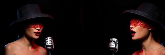 Desgaste de cabelo preto de mulher jovem de raça mista chapéu olhos de cobertura de renda falam para dizer ou gritar, anunciar. a menina canta a música em voz alta com um som poderoso no condensador do microfone. espaço de cópia de fundo escuro de baixa exposição