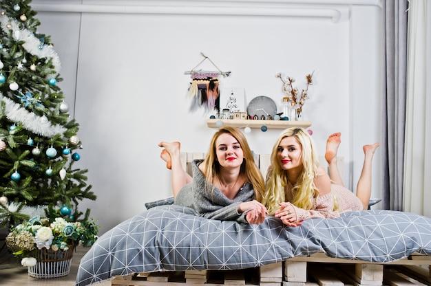 Desgaste de menina loira elegante dois na túnica quente, sentado na cama contra a árvore do ano novo.