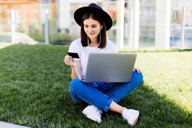 Desgaste de mulher bonita jovem segurando o cartão de crédito e usando o laptop para compra enquanto está sentado na grama verde no parque