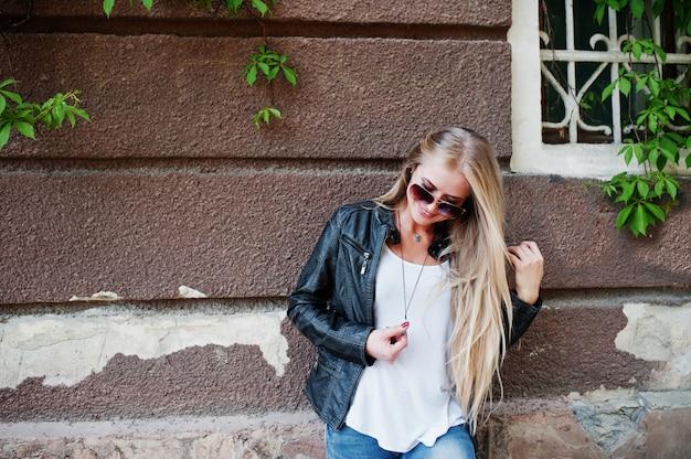 Desgaste de mulher loira elegante em jeans e jaqueta posada na rua contra a parede