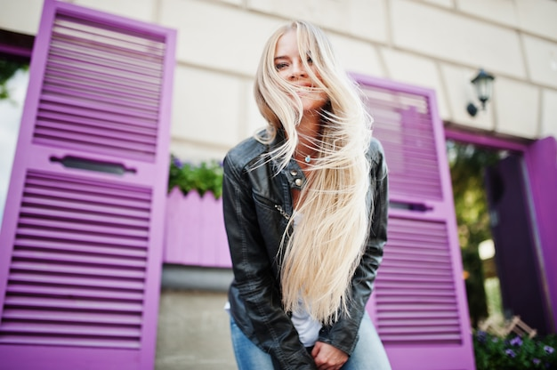 Desgaste de mulher loira elegante em jeans e jaqueta posada na rua contra janela roxa