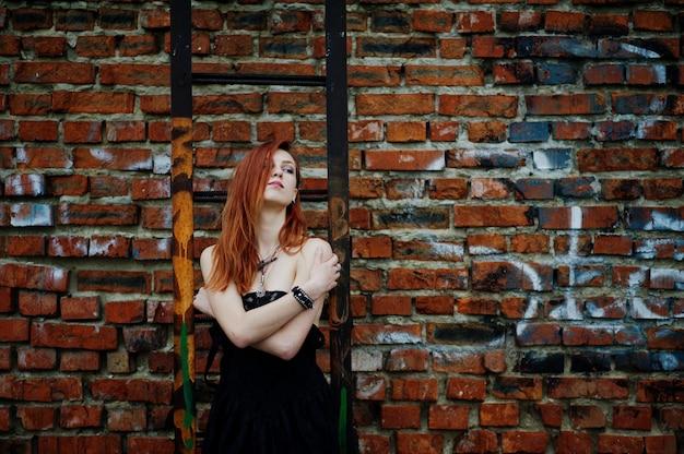Desgaste de mulher punk de cabelo vermelho no vestido preto no telhado contra a parede de tijolos com escada de ferro.