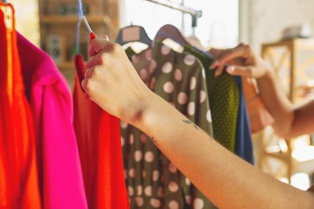Desgaste, loja de roupas durante as vendas, coleção de verão ou outono. feche as mãos experimentando o pano, procurando um novo traje. conceito de moda, estilo, ofertas, emoções, vendas, compras. novo shopping.