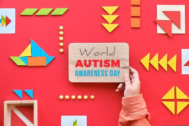 Design criativo para o dia mundial do autismo. mão segure a placa de madeira com texto dia mundial do autismo. elementos tangram espalhados