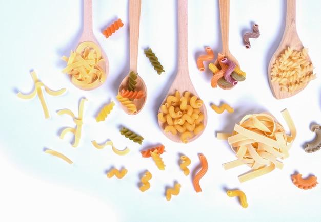 Design de conceito e menu de alimentos italianos. vários tipos de massas farfalle, massas a riso, orecchiette pugliesi, gnocco sardo e farfalle em colheres de madeira, instalação em branco de madeira com configuração plana.