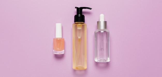 Design de embalagens de cosméticos orgânicos. posição plana, garrafa de bomba de vidro transparente de vista superior, frasco de escova, frasco de soro hidratante em um fundo roxo. cosméticos naturais spa