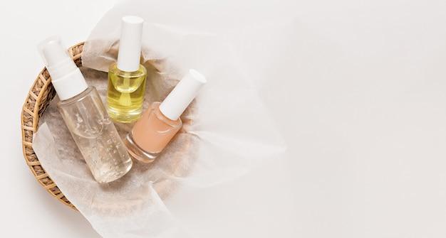 Design de embalagens de cosméticos orgânicos. posição plana, garrafa de bomba de vidro transparente de vista superior, frasco de escova, frasco de soro hidratante em uma cesta de papel em um fundo branco. cosméticos naturais spa