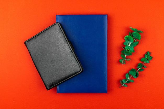 Design de espaço de trabalho criativo e moderno com cadernos de couro preto e azul, área de trabalho de escritório com flores fritas, lay-up plano e foto maquete