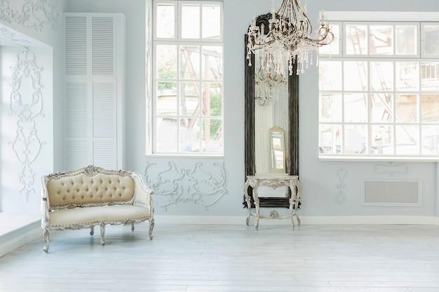 Design de interior luxuoso e rico de sala de estar com móveis clássicos elegantes e decorações de parede. amplo quarto branco claro com grande janela