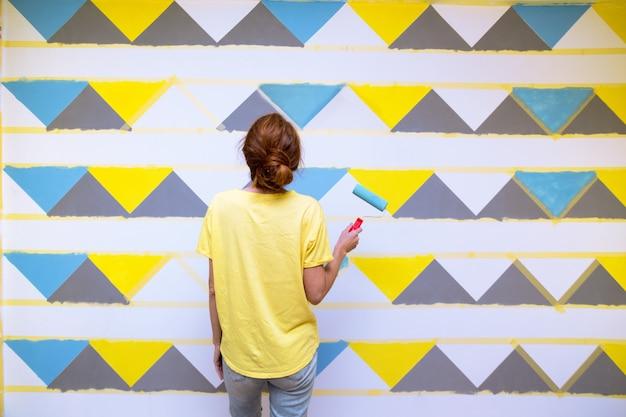 Design de interiores. a garota pinta a parede em padrão geométrico.
