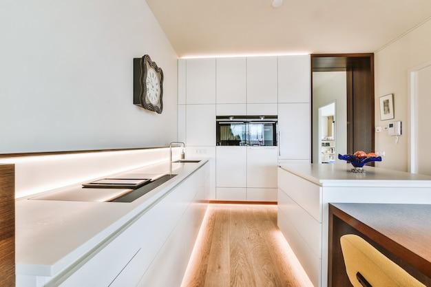 Design de interiores contemporâneo de casa de apartamento moderno leve com cozinha em plano aberto com móveis brancos de estilo minimalista e área de jantar