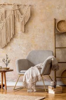Design de interiores da sala de estar oriental com poltrona moderna, macramê, escada de madeira, xadrez, decorações e acessórios pessoais elegantes na decoração elegante da casa. parede wabi sabi.