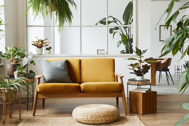Design de interiores de espaço aberto escandinavo com sofá de veludo amarelo, plantas, móveis, livro, cubo de madeira e acessórios pessoais em um cenário doméstico elegante.