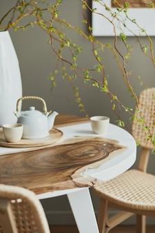 Design de interiores de interiores elegantes de sala de jantar com mesa familiar de madeira e epóxi, cadeiras de vime, flores em um vaso e bule com xícaras. detalhes..