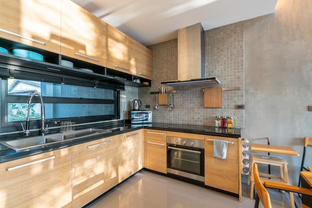 Design de interiores de luxo na área da cozinha com balcão de ilha característica e construído em móveis na casa