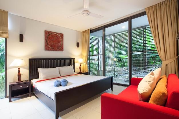 Design de interiores de luxo no quarto da villa piscina com cama king-size.